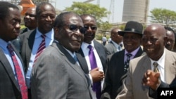 FILE - Zimbabwe's President Robert Mugabe (C-L) greets local chiefs at Zimplats mine, outside Harare.