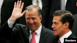 FILE - Jose Antonio Meade waves next to President Enrique Pena Nieto during an event where Pena Nieto announced the resignation of Antonio Meade as finance minister, in Mexico City, Nov. 27, 2017.