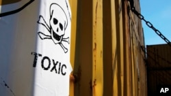 "FILE - A sticker reads ""Toxic"" is seen on containers carrying Syria's dangerous chemical weapons, on the Danish cargo ship, Ark Futura, transporting them out of the strife-torn country, in Cyprus coastal waters, May 13, 2014."