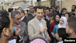 Tổng thống Syria Bashar al-Assad trò chuyện với cư dân trong chuyến thăm làng Ein al-Tinah, đông bắc Damascus, ngày 20/4/2014.
