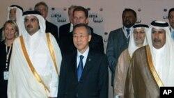 ທ່ານ Ban Ki-Moon ຢືນຢູ່ທາງຂ້າງຈາກອົງມົງກຸດ Sheikh Tamim bin Hamad al-Thani ແຫ່ງ Qatar .ໃນການຖ່າຍຮູບຮ່ວມກັນຂອງບັນດາລັດຖະມົນຕີຕ່າງປະເທດທີ່ມາຮ່ວມກອງປະຊຸມ ທີ່ນະຄອນຫລວງ Doha ວັນທີ 13 ເມສາ, 2011