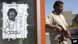利比亚首都的黎波里一个哨卡前,一名反政府武装人员持枪站在卡扎菲的画像旁