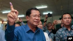 FILE - Cambodian Prime Minister Hun Sen of the Cambodian People's Party shows off his inked finger after voting in local elections at Takhmau polling station in Kandal province, southeast of Phnom Penh, Cambodia, Sunday, June 4, 2017. (AP Photo/Heng Sinith)