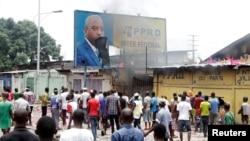Waandamanaji wa upinzani wa DRC wanaonekana wakiharibu mabango yenye picha ya rais Joseph Kabila. Hali ya taharuki liliendelea kutanda huku siku ya uchaguzi ikikaribia.