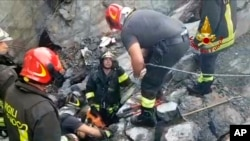 This frame taken from a video released by the Italian firefighters, shows firefighters working on the site of the collapsed Morandi highway bridge in Genoa, northern Italy, Aug. 14, 2018.