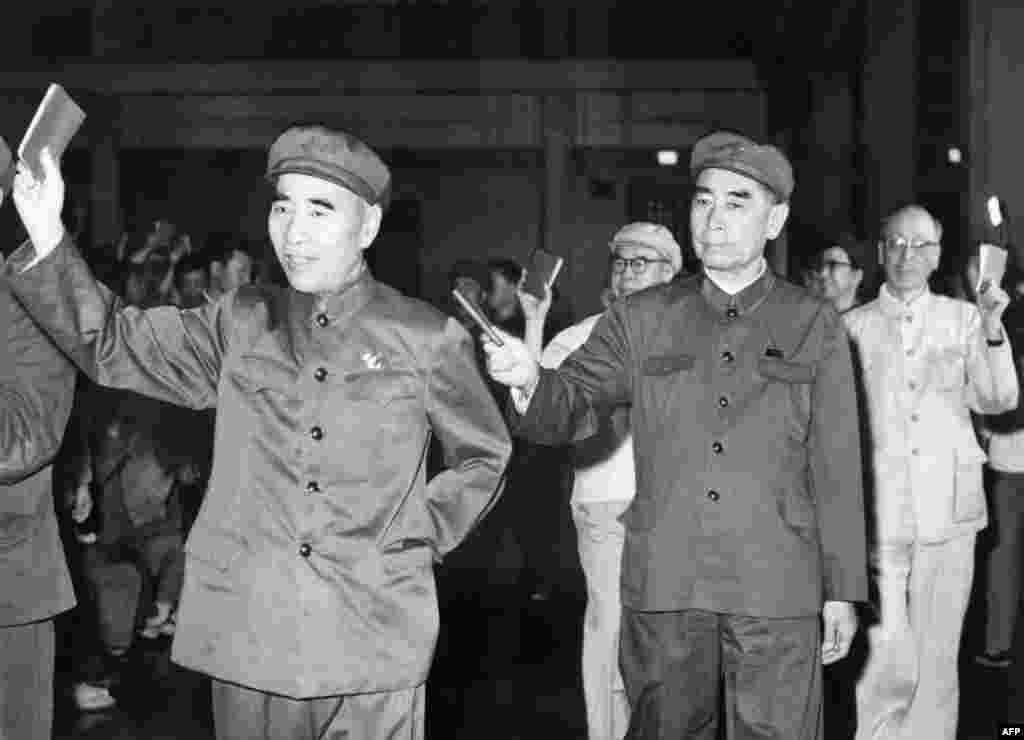"""1967年5月,在北京的一次会议上,5位高官列队,举着毛语录。林彪(1907-1971)在前,周恩来(1898-1976)随后,当时的中共第四号人物、中央文革小组组长陈伯达第三,中共第五号人物、中央文革小组顾问康生第四,毛泽东夫人、中央文革小组副组长江青第五,这显示当时她是中共第六号人物,尽管她连中央委员都不是。后来陈伯达被毛泽东打倒,林彪出逃后也被打倒。江青在毛死后被抓,康生在1980年被开除出党,骨灰被""""开除""""出八宝山。这五个人除了周恩来,都在1980年被列為林彪、江青反革命集团主犯。"""