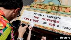 """Manager Donald Melancon memamerkan tiket film """"The Interview"""" di depan gedung biodkop Crest Theater di Los Angeles, California (24/12)."""
