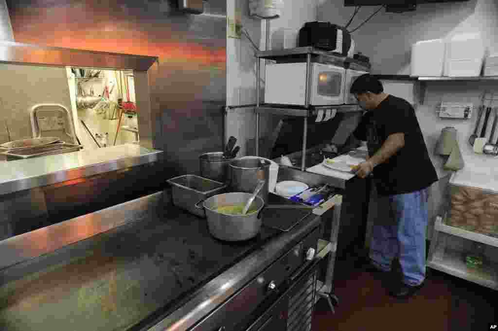 تارکینِ وطن کے بغیر ایک دِن: کارلوس شاویز اپنے ریستوران میں خود ہی کچن سنبھالے ہوئے ہیں۔ ریاست جورجیا کے شہر ایٹلانٹا میں ہسپانوی گروپ نے جمعے، یکم جولائی، 2011ء کو کاروبار بند رکھنے اور اپنی برادری سے کام نہ کرنے اور خریداری پر نہ نکلنے کی کال دی تھی (فائل فوٹو)