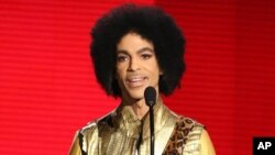FILE - Prince presents the award for favorite album - soul/R&B at the American Music Awards in Los Angeles, Nov. 22, 2015.