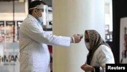 Petugas memeriksa suhu tubuh seorang pengunjung di sebuah pusat perbelanjaan di Teheran, Iran.
