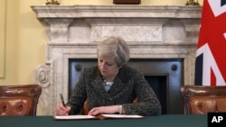 Britain's Prime Minister Theresa May signs the official letter to European Council President Donald Tusk, in 10 Downing Street, London, March 28, 2017, invoking Article 50 of the bloc's key treaty, the formal start of exit negotiations. Britons voted in June to leave the bloc after four decades of membership.