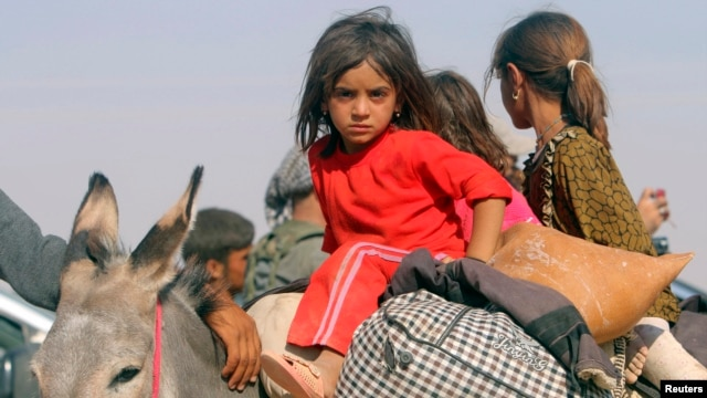 Displaced children from the minority Yazidi sect, fleeing violence from forces loyal to the Islamic State in Sinjar town, ride on a donkey as they head towards the Syrian border, on the outskirts of Sinjar mountain, near the Syrian border town of Elierbeh, Aug. 11, 2014.