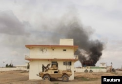 Smoke billows from a building after a Taliban attack in Gereshk district of Helmand province, Afghanistan on March 9, 2016.