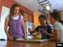 Wafaa Elmahgob cooks with her daughter, Nourene Nabbus, and her niece. (VOA)