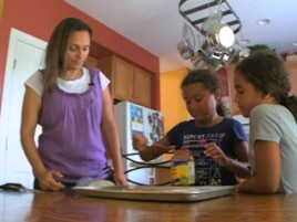 Wafaa Elmahgob cooks with her daughter, Nourene Nabbus, and her niece. (VOA)