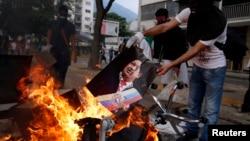 Un manifestante quema un cartel con la imagen de Hugo Chávez durante protestas en Caracas.