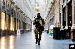 FILE - In this Thursday, Nov. 26, 2015 file photo, a Belgian Army soldier walks through the Galleries Royal Saint-Hubert in the center of Brussels. Some experts say it will take months for Europeans to psychologically adapt to life after the Paris attacks.