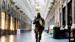 FILE - In this Nov. 26, 2015 file photo, a Belgian Army soldier walks through the Galleries Royal Saint-Hubert in the center of Brussels.