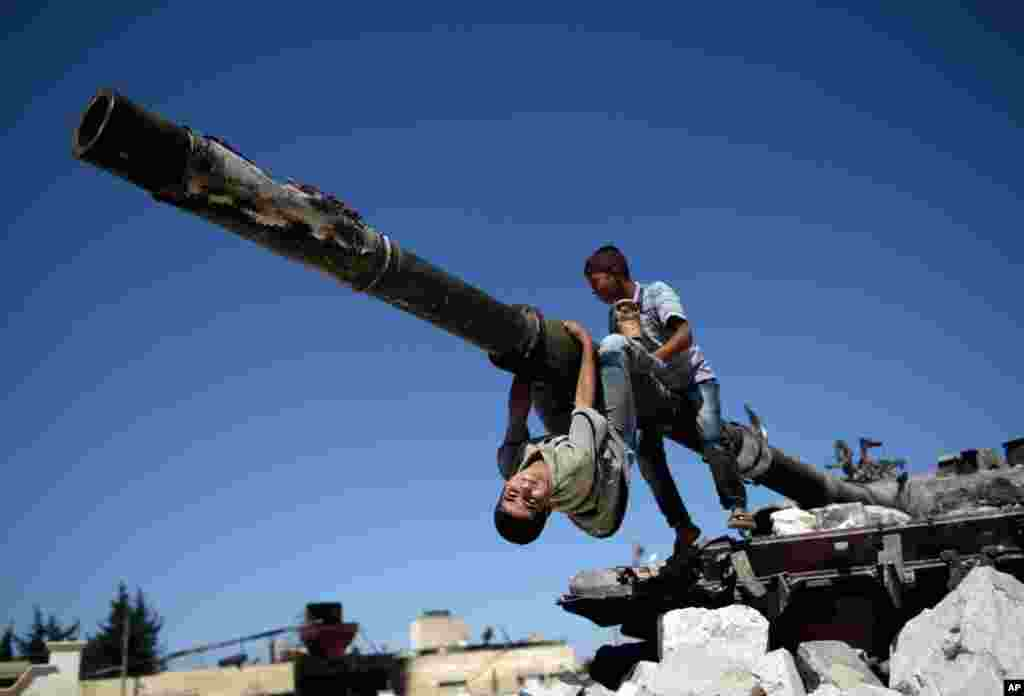 Boys play on a Syrian military tank (destroyed during fighting with the rebels), in Azaz, September 2, 2012.
