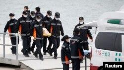 Nhân viên dịch vụ khẩn cấp mang thi thể nạn nhân từ chiếc phà bị chìm lên xe cứu thương tại cảng Jindo, ngày 22/4/2014.