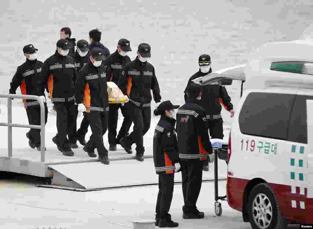 22일 긴급구조 대원들이 진도 해상에서 침몰한 여객선 세월호에서 발견된 사체를 옮기고 있다.
