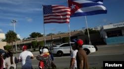 美國佛羅里達州邁阿密,大眾手舉美國和古巴國旗走過一家古巴風味的餐館。(2021年7月18日)