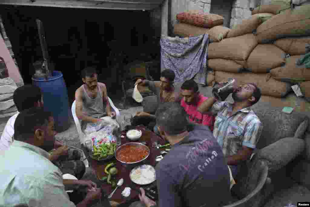 Free Syrian Army fighters eat their iftar meal as they break fast, in Aleppo's Karm al-Jabal neighborhood, July 21, 2013.