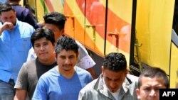 Salvadoreños deportados de los Estados Unidos se bajaron de un autobús, a su llegada al Centro de Atención a Migrantes en San Salvador el 22 de junio de 2018.