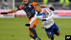 Adbelhamid El Kaoutari de Montpellier (à gauche) aux prises avec Alexandre Lacazette de Lyon (à droite) au cours d'un match de football de la ligue française, au stade de Gerland, à Lyon, France, le 1er décembre 2012.