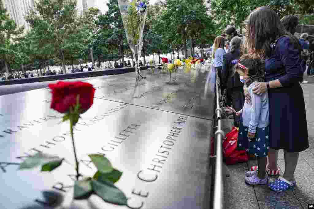 អ្នកកាន់ទុក្ខ បានឈរមើលឈ្មោះដែលបានឆ្លាក់ទុកនៃអ្នកដែលបានស្លាប់កាលពីថ្ងៃទី១១ ខែកញ្ញា ឆ្នាំ២០០១ នៅឯសារមន្ទីរជាតិនិងទីរំឭកវិញ្ញាណក្ខន្ធជនដែលបានស្លាប់កាលពីថ្ងៃទី១១ ខែកញ្ញា ឆ្នាំ២០០១ (National September 11 Memorial and Museum) នៅថ្ងៃសុក្រ ទី១១ ខែកញ្ញា ឆ្នាំ២០២០ នៅទីក្រុងញូវយ៉ក។ (AP)