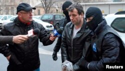 FILE - Marcel Lazar Lehel, 40, is escorted by masked policemen in Bucharest, after being arrested in Arad, west of Bucharest, Romania, Jan.22, 2014.
