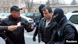 FILE - Marcel Lazar Lehel, 40, is escorted by masked policemen in Bucharest, after being arrested in Arad, west of Bucharest, Romania, Jan. 22, 2014.