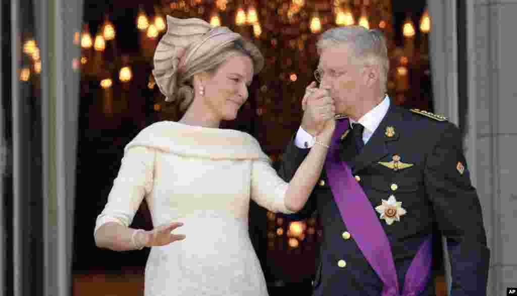 Belgium's King Philippe, right, kisses the hand of Queen Mathilde as they stand on the balcony of the royal palace in Brussels. Philippe has taken the oath before parliament to become the country's seventh king after his father Albert abdicated.
