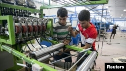 Palestinians work at a textile factory in the Industrial Park of the West Bank Jewish settlement of Barkan, Nov. 8, 2015.