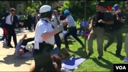 FILE - Police in Washington try to break up a clash between protesters and supporters of Turkish President Recep Tayyip Erdogan near the Turkish ambassador's residence, May 16, 2017, in this still image from video.