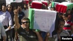 Palestinians carry flag-covered coffins containing the remains of Palestinian militants