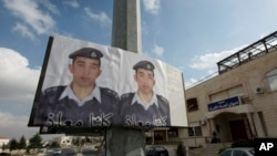 FILE - Two posters with pictures of Jordanian pilot Lt. Muath al-Kaseasbeh hang on a street pole, in front of the pilot's tribal gathering place, in Amman, Jordan,