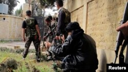 Free Syrian Army fighters carrying weapons, take up position during clashes with forces loyal to Syria's President Bashar al-Assad in the Khan al-Assal area, near Aleppo Apr. 20, 2013.