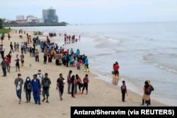 Warga berkumpul di pantai untuk membersihkan pantai dari tumpahan minyak di Pantai Kilang Mandiri di Balikpapan, Kalimantan Timur, 4 April 2018. (Foto: Antara/Sheravim via REUTERS)