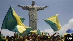 Các thiếu niên Brazil vui mừng dưới tượng Chúa Cứu thế ở Rio de Janeiro khi Brazil được FIFA trao cho quyền đăng cai World Cup 2014, ngày 30 tháng 10, 2007