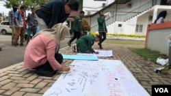 Mahasiswa Universitas Sumatera Utara (USU) saat menandatangani seruan penolakan terhadap tindak pelecehan seksual di kampus, Jumat (21/6). (VOA/Anugrah Andriansyah)