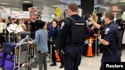 Police direct arriving passengers past dozens of pro-immigration demonstrators who cheer and hold signs at Dulles International Airport, to protest President Donald Trump's travel ban in Chantilly, Virginia, in suburban Washington, Jan. 29, 2017.