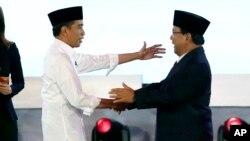 Presiden Joko Widodo (kiri) dan capres Prabowo Subianto usai debat pilpres di Jakarta, 17 Juni 2019. (Foto: AP)