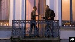 Mohammad Abdeslam, à gauche, frère de Salah et Brahim Abdelslam, auteurs présumés des attaques de Paris, allume des bougies avec un homme non identifié sur le balcon de sa maison à Molenbeek, Belgique 18 novembre 2015.