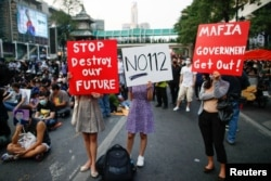 Pro-democracy protesters hold signs during a rally demanding the release of arrested protest leaders and the abolition of 112 lese majeste law, in Bangkok, Thailand, March 24, 2021.