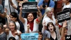 2018年6月28日,在华盛顿国会山的哈特参议院办公大楼内,妇女们抗议移民的子女与父母被分开的情况。