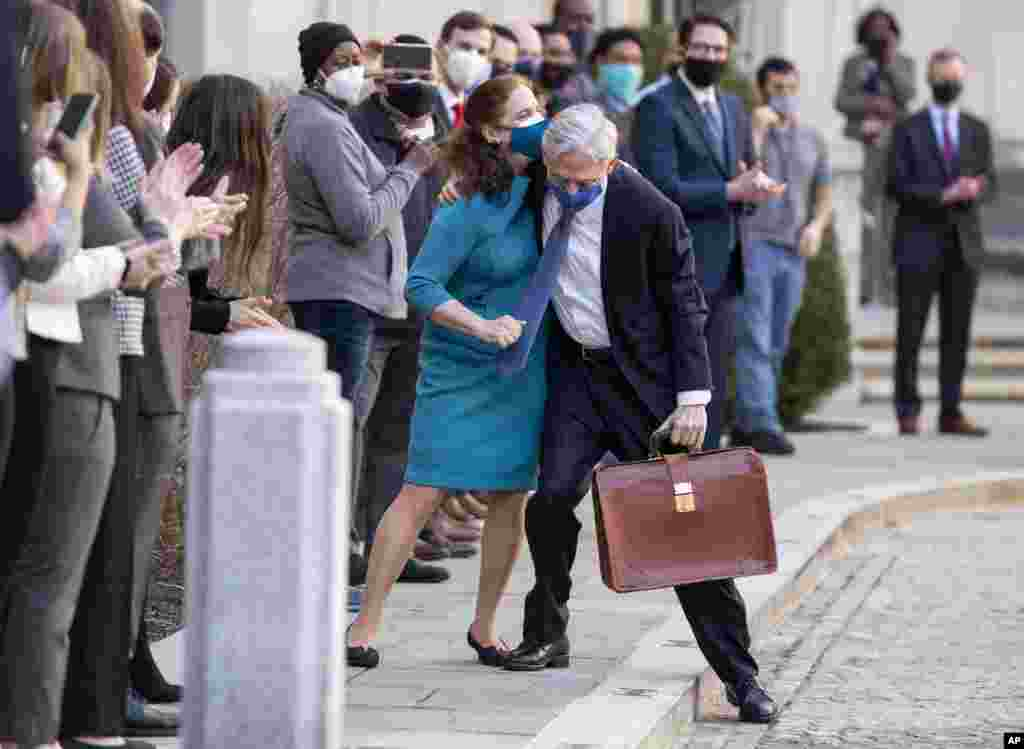 President Joe Biden's pick for attorney general Merrick Garland hugs his wife Lynn as he arrives for his first day at the Department of Justice in Washington, D.C.