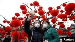Du khách đeo khẩu trang chống ô nhiễm chụp ảnh lưu niệm ngày đầu năm mới tại Bắc Kinh, Trung Quốc, ngày 28 tháng 01 năm 2017.
