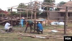 Workers use locally available material to put up a new structure at the orphanage. (S.P. Apiku/VOA)