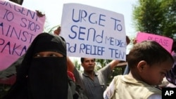 An ethnic Rohingya refugee holds up a poster during a demonstration calling for the end to the sectarian violence in Burma, in Medan, North Sumatra, Indonesia, Wednesday, June 13, 2012.